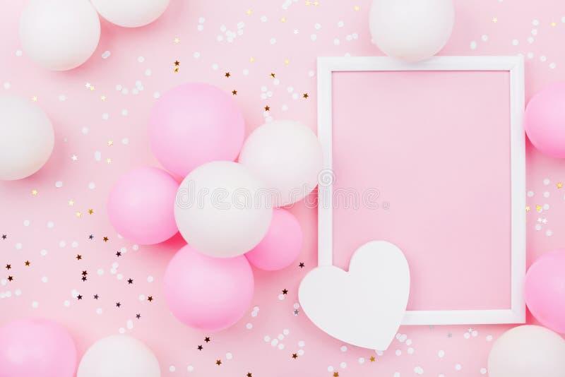 与框架、淡色气球、心脏和五彩纸屑的假日或生日大模型在桃红色台式视图 平的位置构成 免版税库存图片