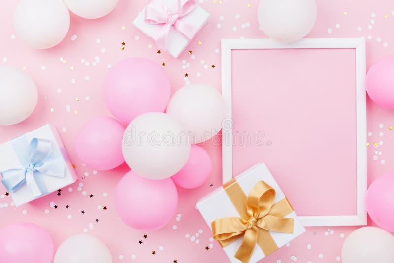 与框架、礼物盒、淡色气球和五彩纸屑的生日大模型在桃红色台式视图 平的位置构成 库存照片