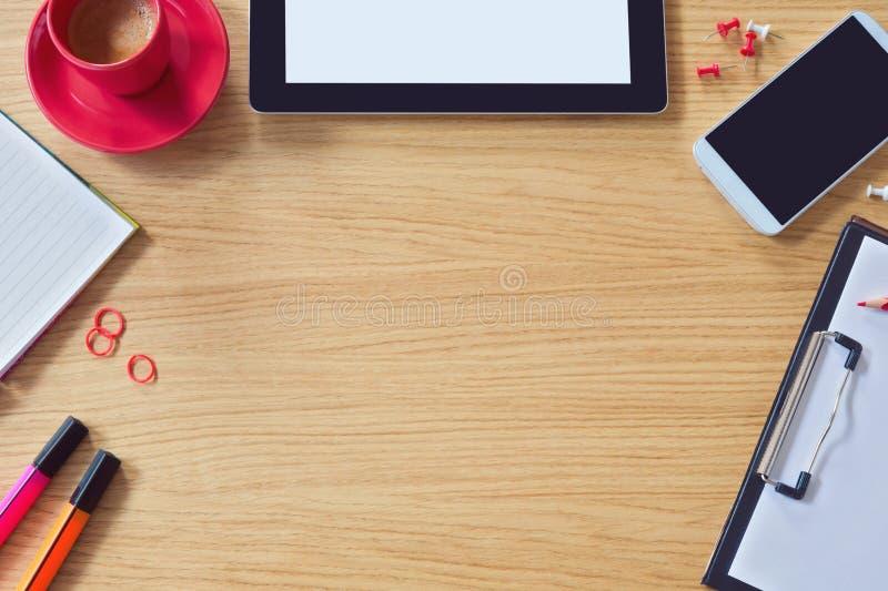 与桌、巧妙的电话、笔记薄和咖啡杯的现代办公室桌背景 看法从上面与拷贝空间 免版税库存图片