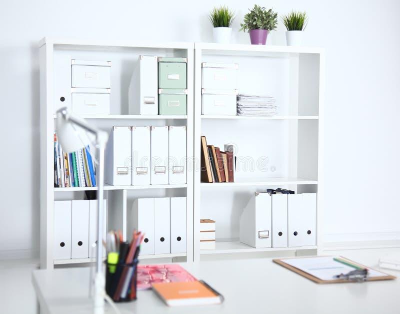 与桌、椅子和书橱的现代办公室内部 免版税库存照片