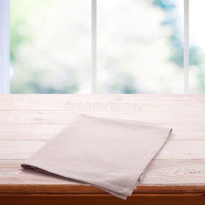 与桌布的空的木桌 餐巾接近的顶视图嘲笑 与窗口的厨房土气背景 库存照片