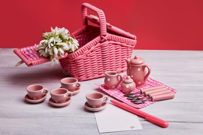 与桌设置和snowdrops的野餐卡片,与空白的便条纸、银器,桃红色和白色方格的餐巾 库存图片