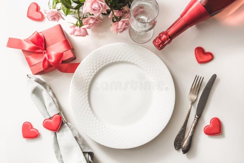 与桌餐位餐具的情人节晚餐与红色礼物,香槟的玻璃,一个瓶香槟,桃红色玫瑰,心脏orname 库存图片