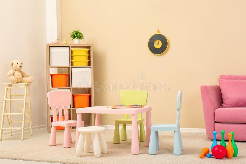 与桌,沙发的舒适孩子室内部 免版税库存图片