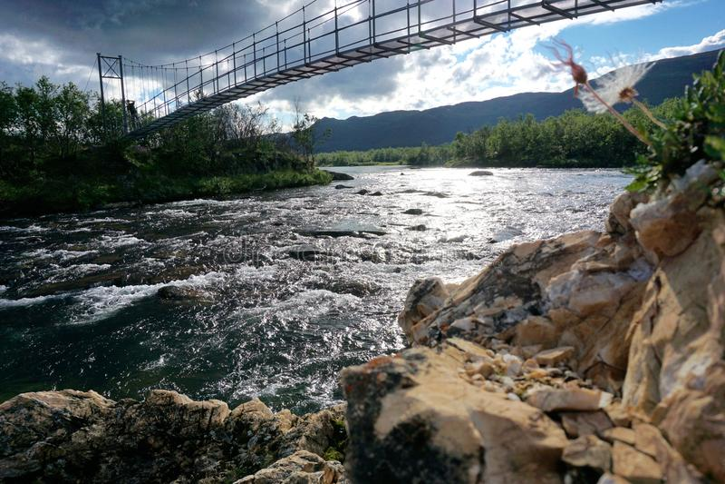 与桥梁的安全段落在连续河,拉普兰,阿比斯库国家公园,瑞典 库存照片
