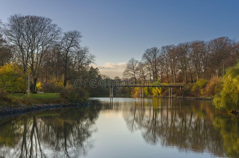 与桥梁的秋天风景在湖 免版税库存照片