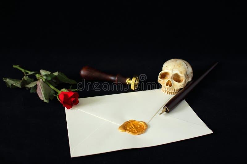 与桶的消息信件在一朵红色玫瑰和一块邪恶的人的头骨陪同的黑背景 库存照片
