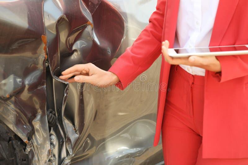 与检查残破的汽车的片剂的保险代理公司 免版税库存照片