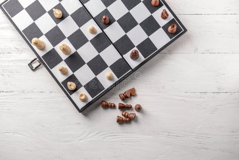 与棋子的比赛板在白色木桌上 免版税库存照片