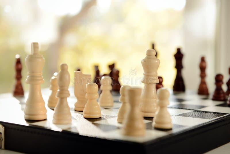 与棋子的比赛板在窗台 图库摄影