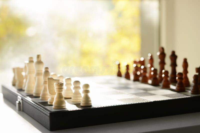 与棋子的比赛板在窗台 免版税库存照片