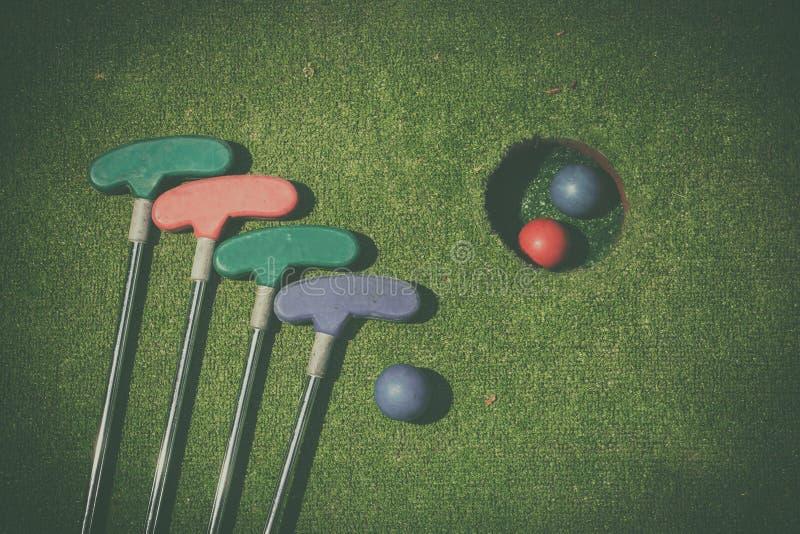 与棒和球的小小高尔夫球孔 免版税图库摄影