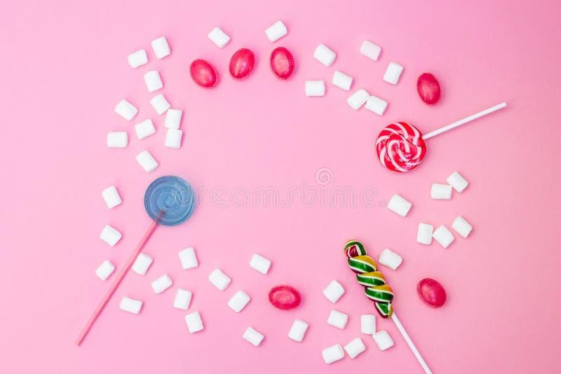与棒棒糖和蛋白软糖框架的平的被放置的文本的构成和空间在桃红色背景 免版税库存照片