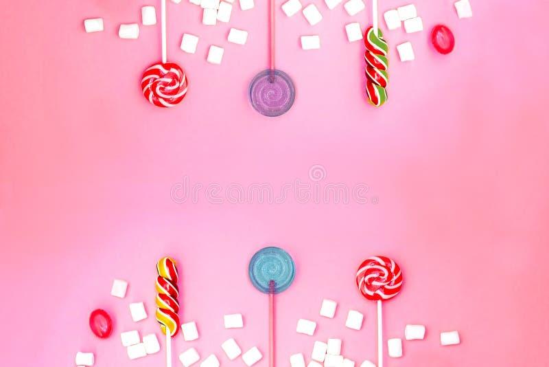 与棒棒糖和蛋白软糖框架的平的被放置的文本的构成和空间在桃红色背景 免版税库存图片