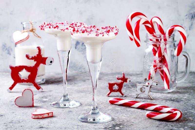 与棒棒糖外缘的白色巧克力薄荷马蒂尼鸡尾酒 圣诞节节日晚会饮料 免版税图库摄影