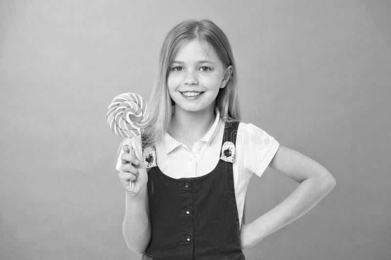 与棒棒糖的女孩微笑在紫罗兰色背景 愉快的孩子用在紫色背景的漩涡焦糖 儿童小微笑 免版税库存照片