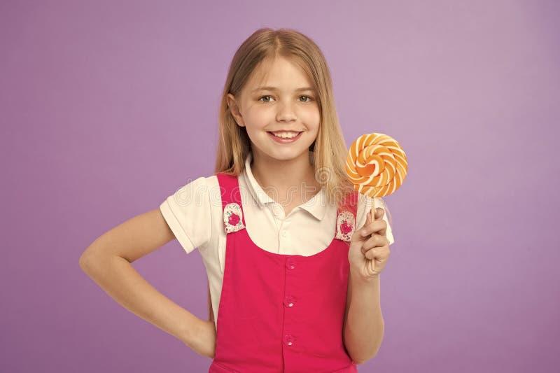 与棒棒糖的女孩微笑在紫罗兰色背景 愉快的孩子用在紫色背景的漩涡焦糖 小儿童微笑 图库摄影