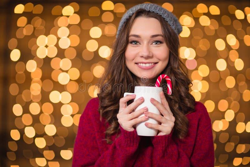 与棒棒糖的有吸引力的愉快的卷曲少妇饮用的咖啡 图库摄影
