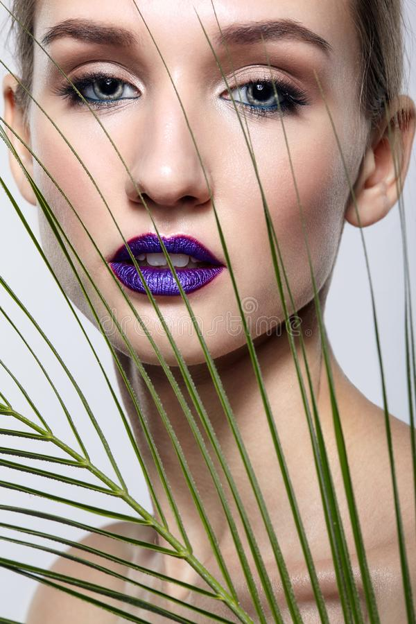 与棕榈分支叶子的女性画象在前景和秀丽与紫罗兰色嘴唇的面孔构成 免版税库存照片