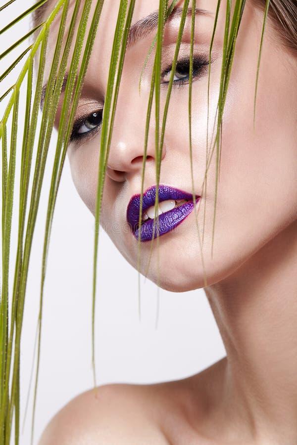 与棕榈分支叶子的女性画象在前景和秀丽与紫罗兰色嘴唇的面孔构成 免版税图库摄影
