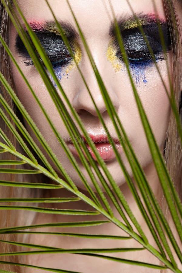与棕榈分支叶子的女性画象在前景和秀丽面孔构成 图库摄影