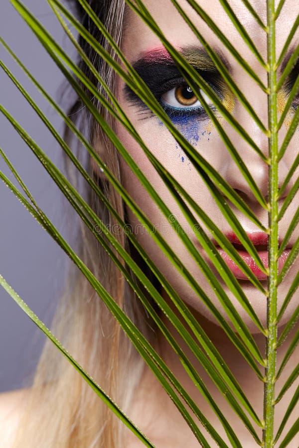 与棕榈分支叶子的女性画象在前景和秀丽面孔构成 库存图片