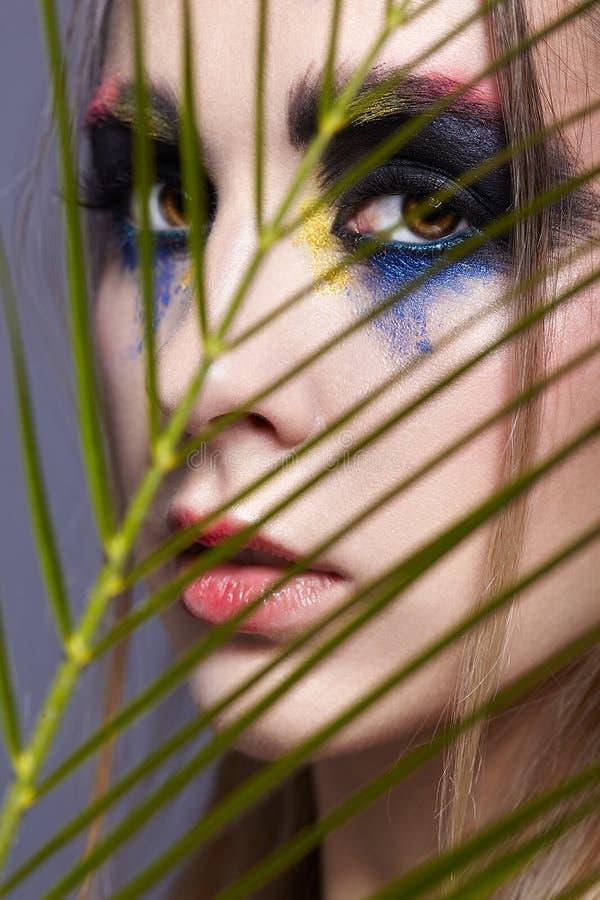与棕榈分支叶子的女性画象在前景和秀丽面孔构成 免版税库存照片