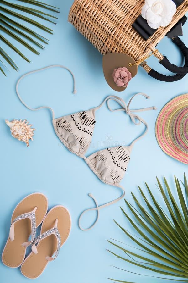 与棕榈叶的夏天背景,时尚帽子,比基尼泳装,触发器,秸杆在轻的淡色蓝色背景的海滩袋子,旅行和 免版税库存图片
