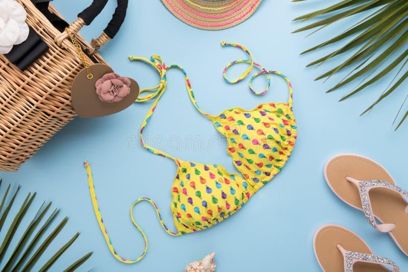 与棕榈叶的夏天背景,时尚帽子,比基尼泳装,触发器,秸杆在轻的淡色蓝色背景的海滩袋子,旅行和 库存照片