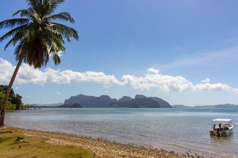 与棕榈和小船的热带海滩有uknown人的 美丽的盐水湖在菲律宾 ?? 亚洲旅行 库存照片