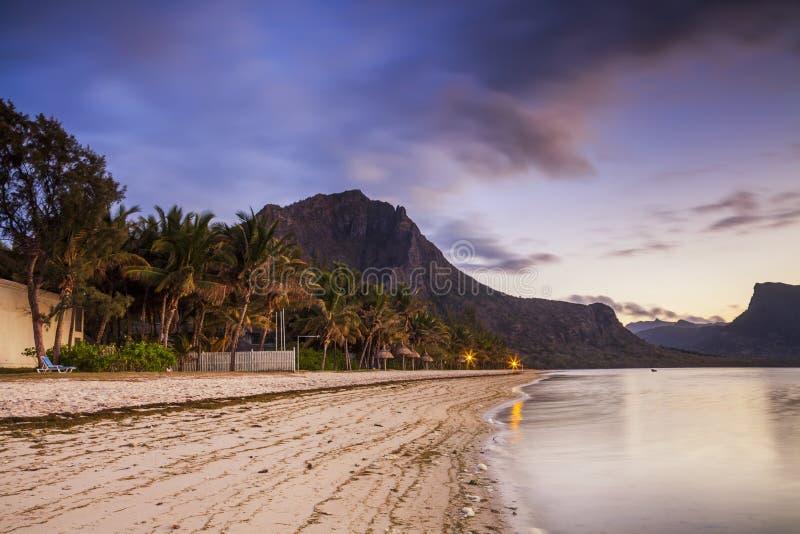 与棕榈树和山的天堂沙滩在日落 免版税库存图片