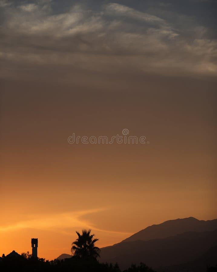 与棕榈树的日落风景和小山,点心喜欢 免版税图库摄影