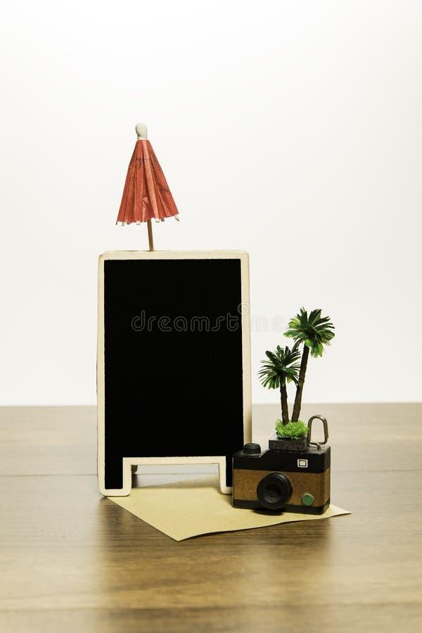 与棕榈树的木照相机和有红色伞的空白的黑人委员会 库存照片