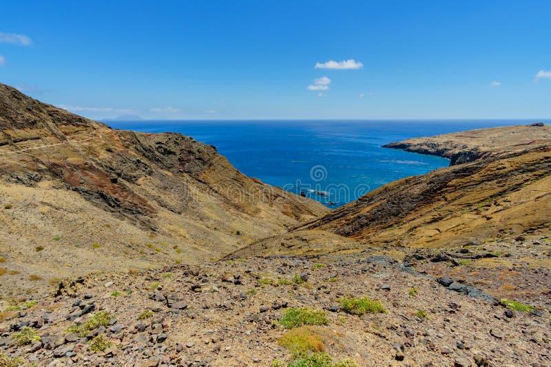 与棕榈的干燥沙漠风景和山和海洋在背景中在马德拉岛 库存照片