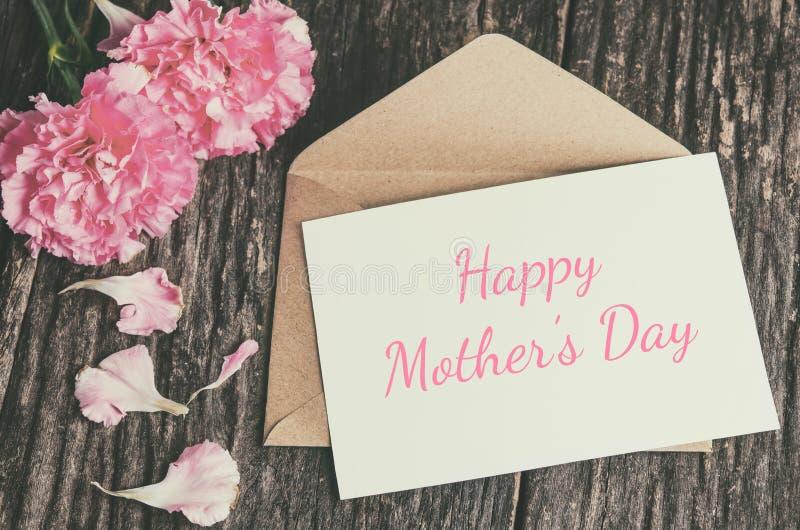 与棕色信封和桃红色康乃馨f的愉快的母亲` s天卡片 免版税库存照片