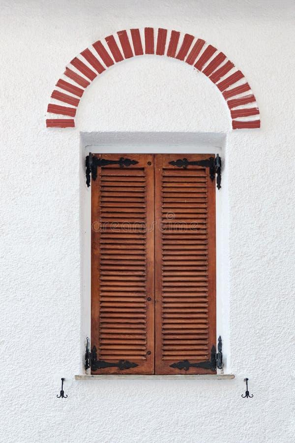 与棕色快门的希腊木葡萄酒窗口 免版税库存照片