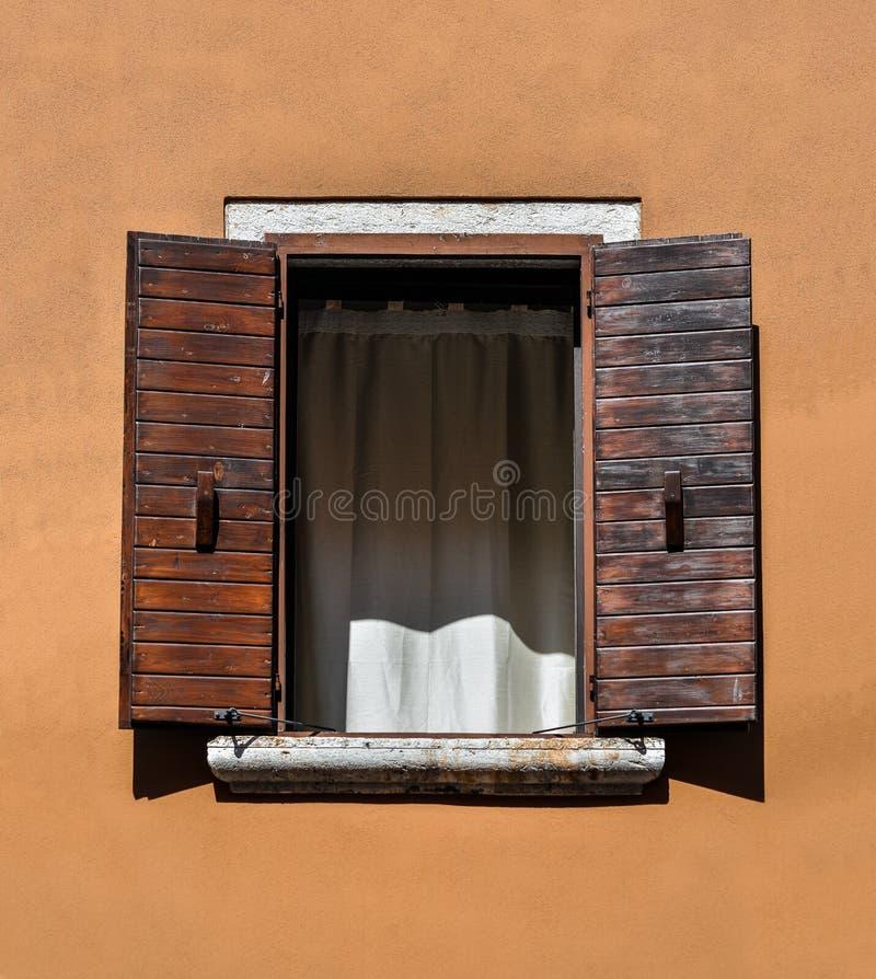 与棕色木快门和明亮的赤土陶器墙壁的美好的老窗架 农村或古色古香的窗架 设计要素例证图象向量 T 免版税库存照片