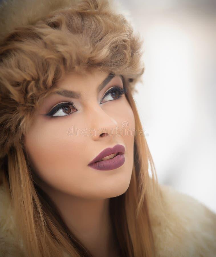 与棕色毛皮盖帽的可爱的年轻白种人成人 有华美的戴裘皮帽的嘴唇和眼睛的美丽的白肤金发的女孩,室外 图库摄影