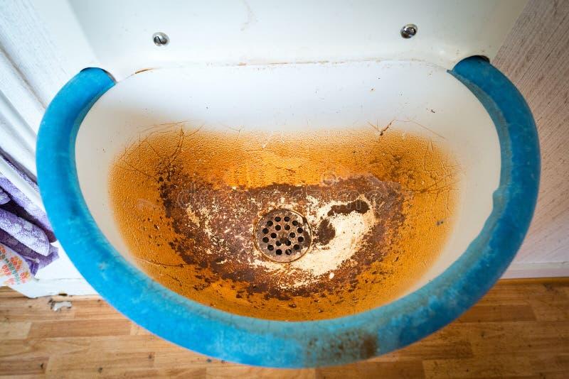 与棕色污点的老肮脏的水槽 库存图片