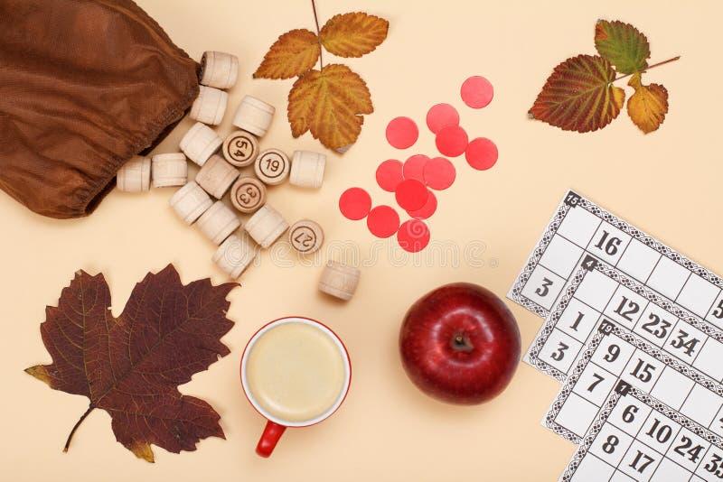 与棕色袋子、游戏卡、咖啡和苹果的木乐透纸牌桶在米黄背景 秋天题材 库存照片