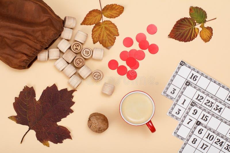 与棕色袋子、游戏卡和咖啡的木乐透纸牌桶在米黄背景的 秋天题材 库存照片