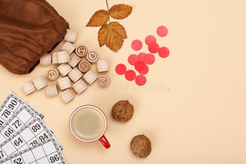 与棕色袋子、游戏卡和咖啡的木乐透纸牌桶在米黄背景的 秋天题材 免版税库存照片