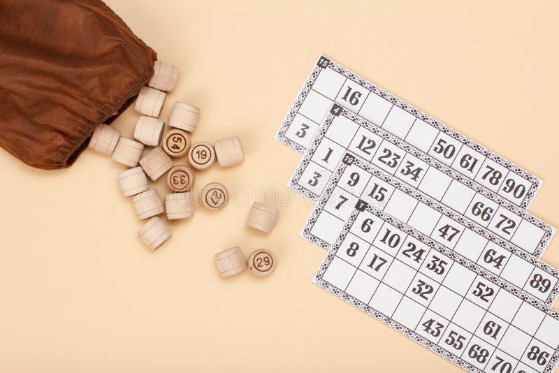 与棕色袋子的木乐透纸牌桶和在米黄背景的游戏卡 库存照片