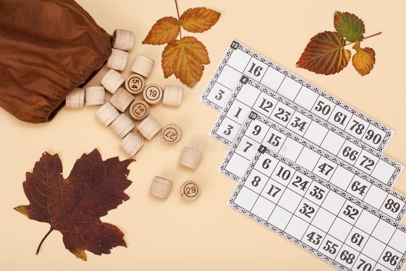 与棕色袋子的木乐透纸牌桶和在米黄背景的游戏卡 免版税图库摄影