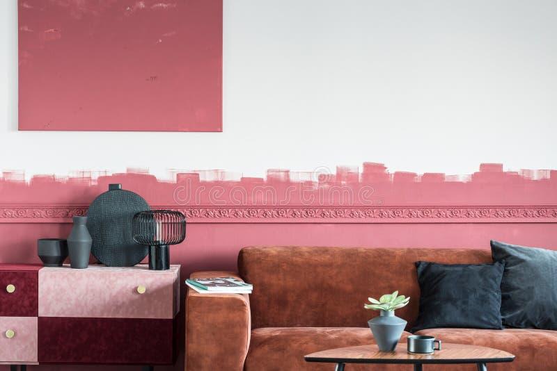 与棕色长沙发和白色和红色ombre墙壁的典雅的客厅内部 图库摄影