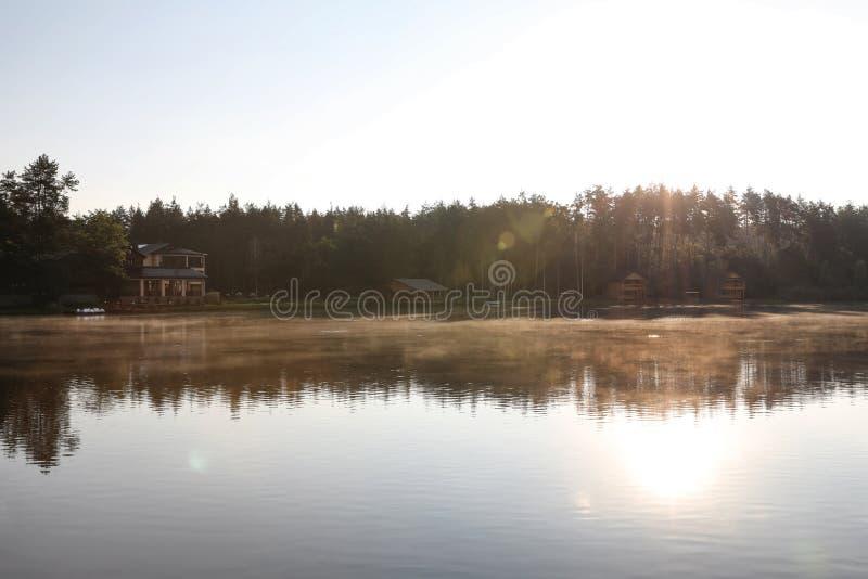 与森林的美好的风景和房子临近湖 野营的季节 库存图片