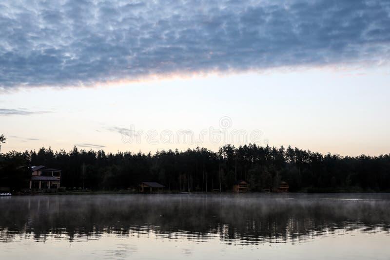 与森林的美好的风景和房子临近湖 库存照片