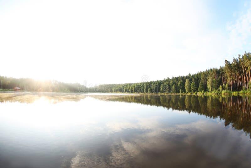 与森林的美好的风景和房子临近湖 免版税库存图片