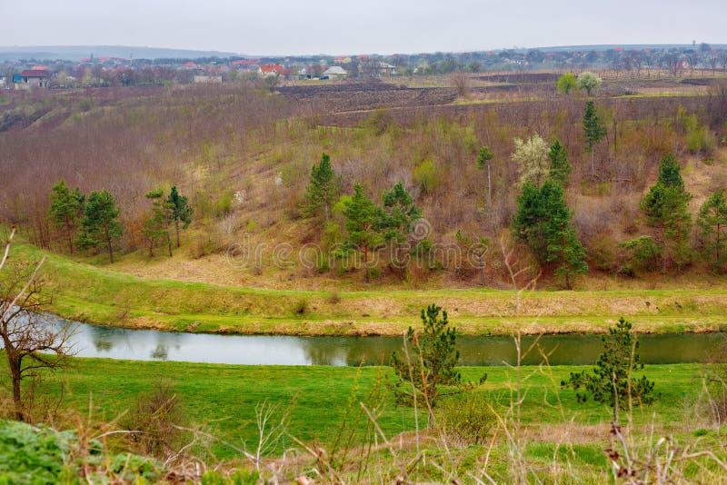 与森林,河的美好的农村春天风景在多云下雨天 库存照片
