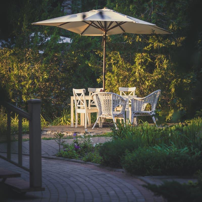 与椅子和舒适的藤条椅子的偏僻的桌在绿色植被中的一把阳伞下作为晚餐的一个舒适地方 库存图片
